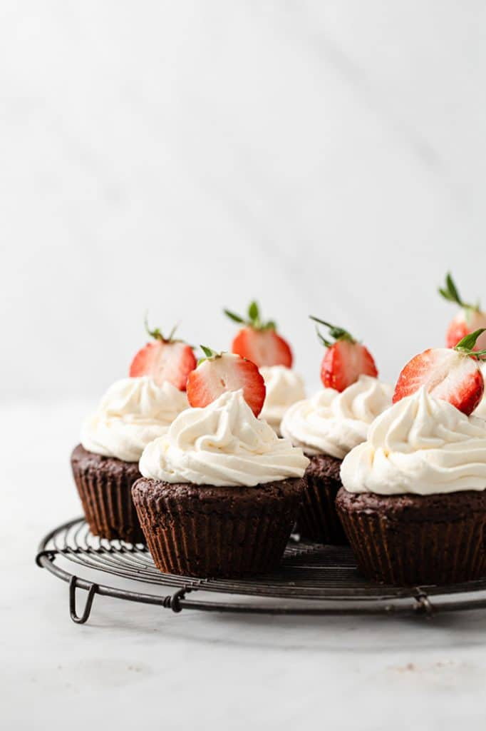 close-up image of 7 chocolate strawberry cupcakes topped with slice strawberries resting on a wire-rack atop a marble kitchen counter