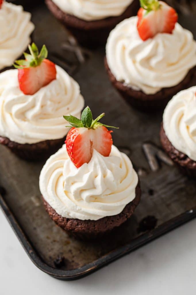 close-up angled image of a chocolate strawberry cupcake on a baking tray atop a marble kitchen table