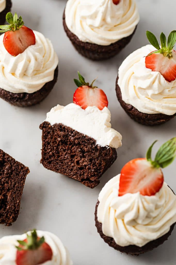 6 chocolate strawberry cupcakes topped with sliced strawberries with a half eaten cupcake on the middle atop a marble kicthen counter