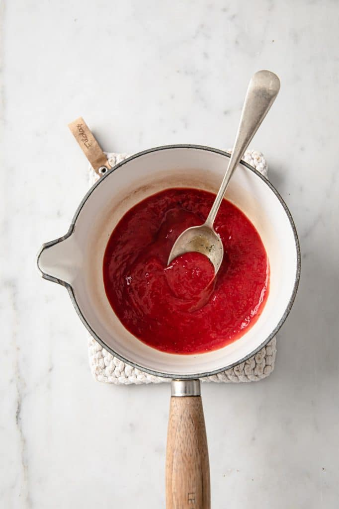 strawberry puree in a saucepan being stirred with a spoon atop a marble kitchen counter