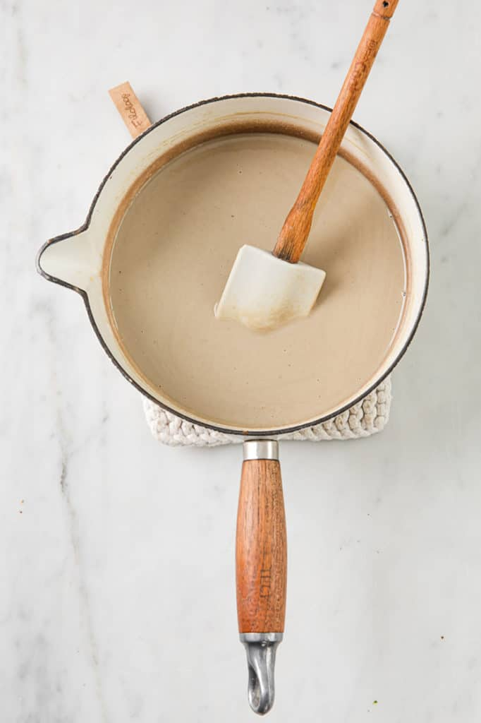 melted SunButter and coconut oil in a sauce pan being stirred with a rubber spatula
