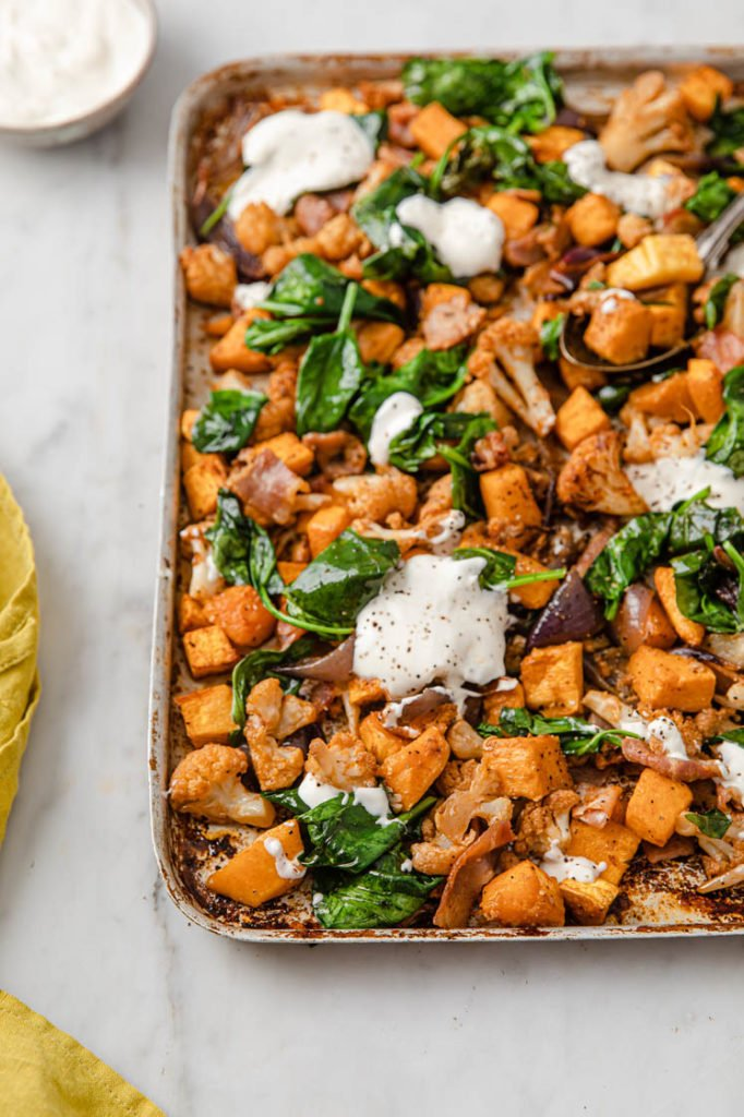 an angled image of a baking tray of roasted butternut squash and cauliflower and bacon topped with sour cream, a rolled yellow napkin and a bowl of sour cream on the left hand corner atop a marble kitchen counter