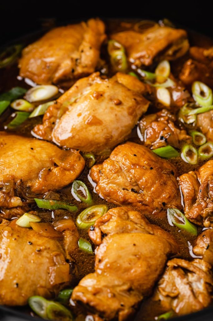 close-up shot of cooked chicken thighs with spring onion in chicken adobo sauce
