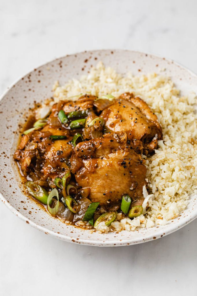 close-up image of a bowl of cauliflower rice topped with chicken adobo atop a marble kitchen counter