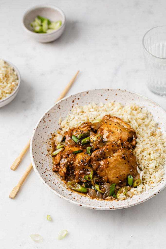 a bowl of cauliflower rice topped with chicken adobo with a pair of chopsticks place on the left sie atop a marble kitchen counter