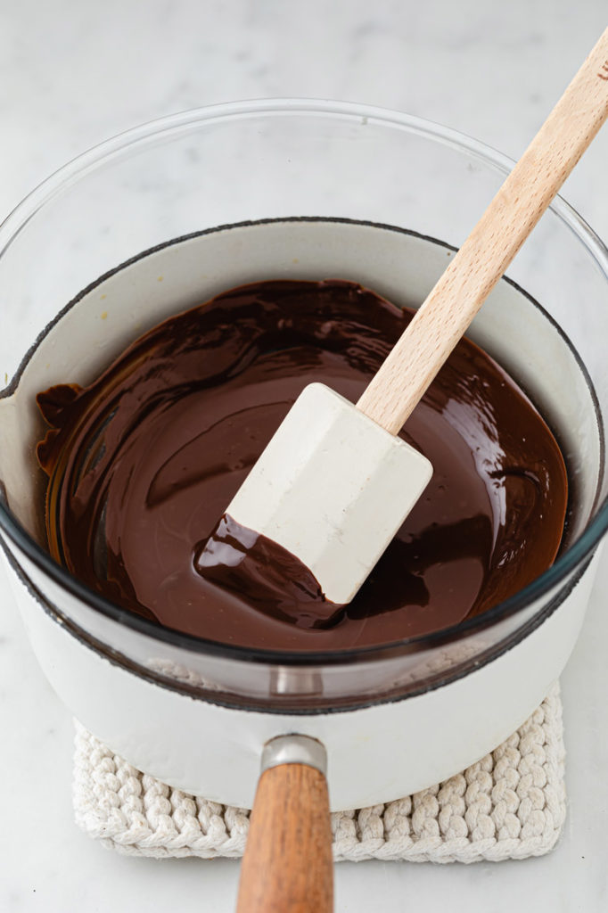 dark chocolate bars melted in a large pot using the double boiler method while being stirred with a rubber spatula atop a marble kitchen counter
