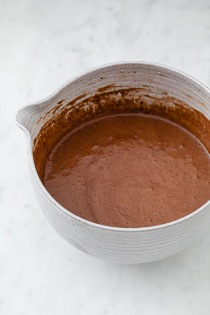 chocolate lave cake batter in a mixing bowl atop a marble kitchen counter