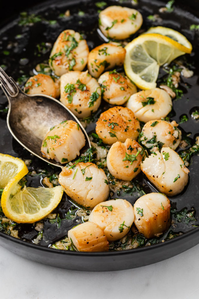 scallop scooped by a spoon from a pan of cooked scallops with lemon slices atop a marble kitchen counter