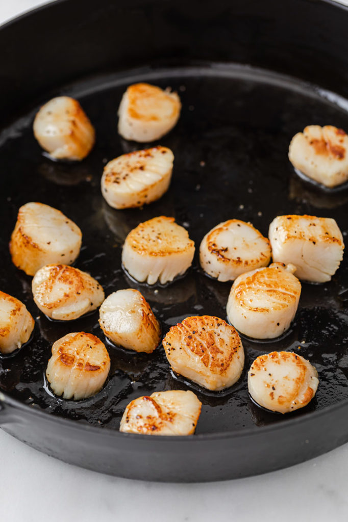 scallops being cooked in a cast iron pan