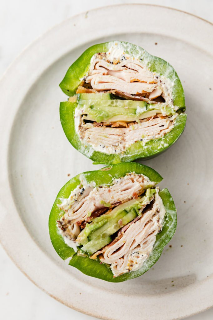 close-up image of 2 green bell pepper sandwich on a ceramic plate atop a marble kitchen counter
