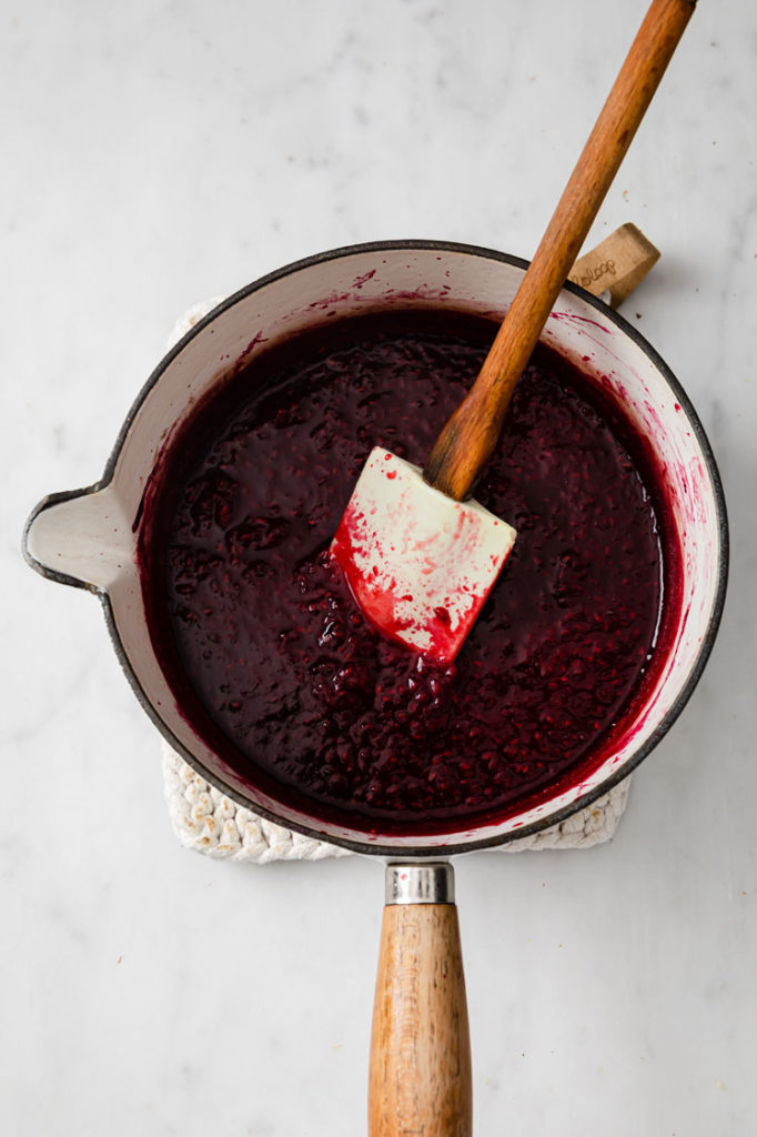 raspberries being crushed by the back of a rubber spatula in a saucepan