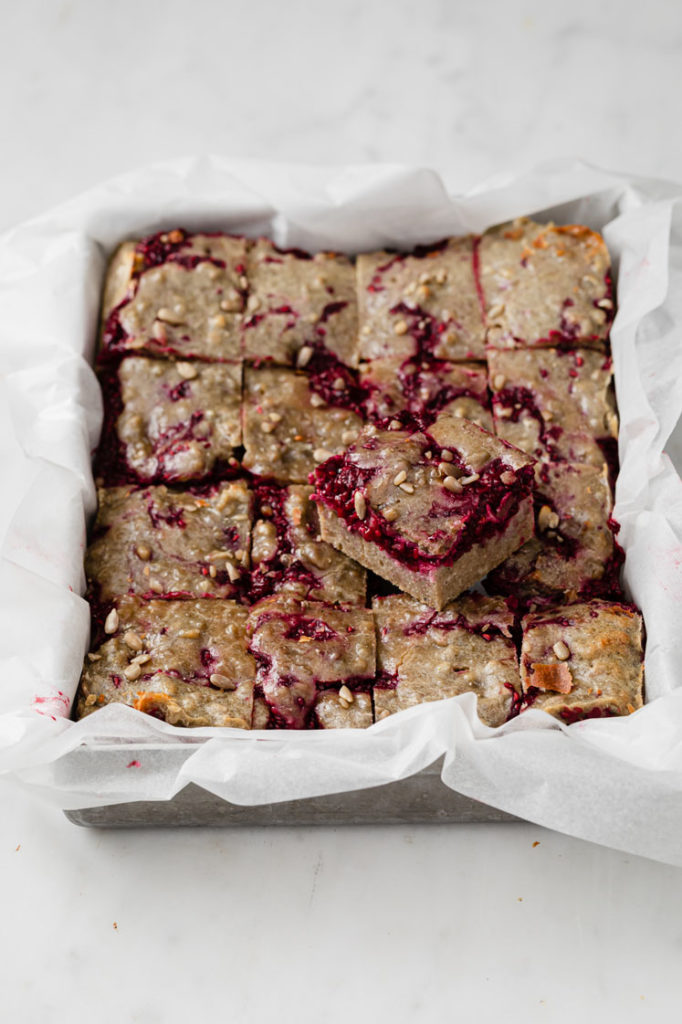 featured image of keto raspberry crumble bars straight out of the oven atop a marble kitchen counter