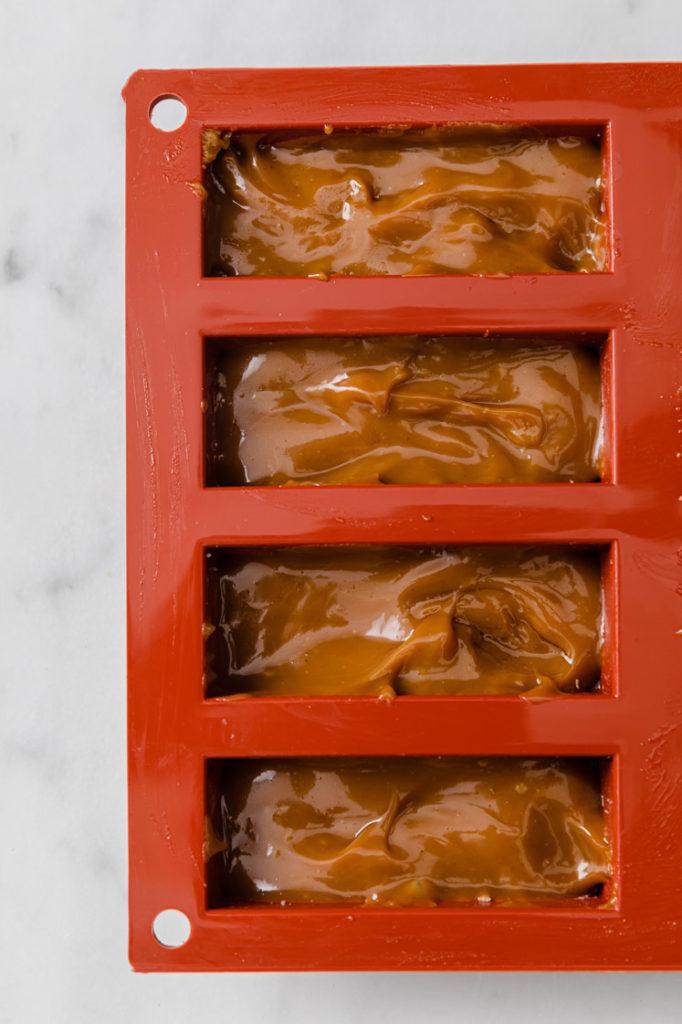caramel poured atop twix copycat mixture in a rectangular silicone mold