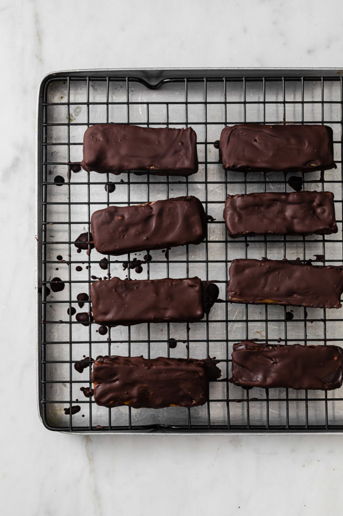 keto twix bars resting on top of a wire rack atop a marble kitchen counter