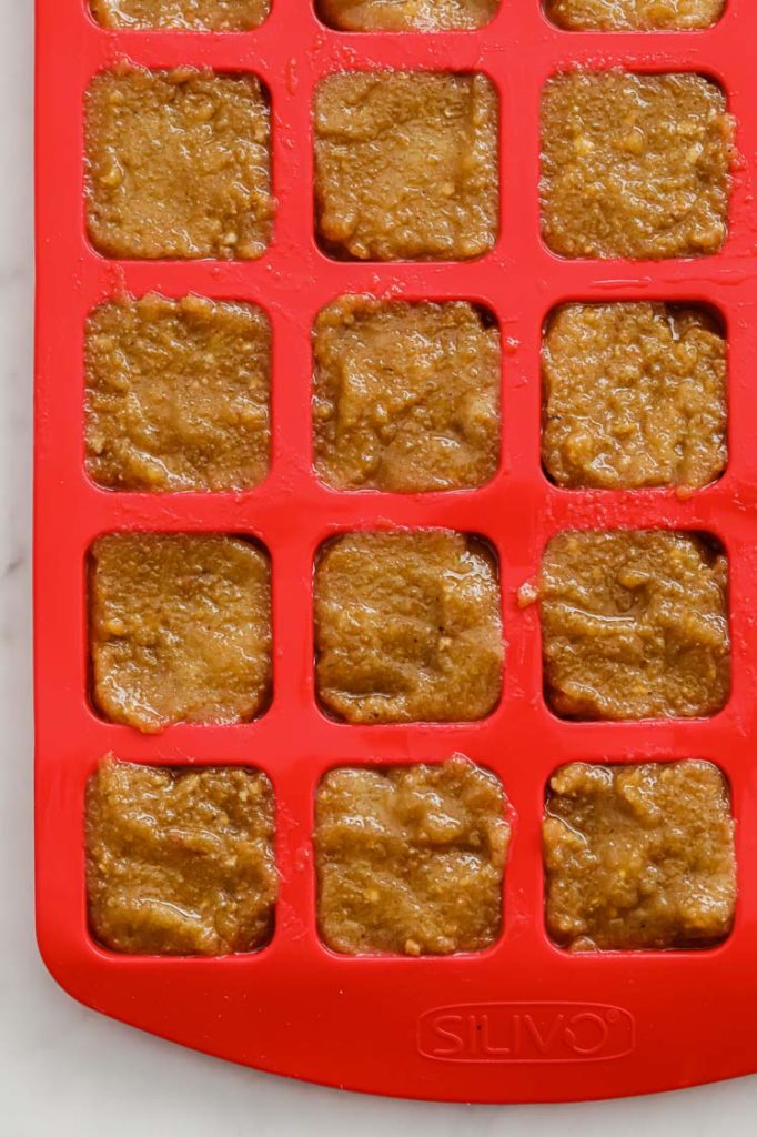 Butterfinger layer poured in a square silicon mold atop a marble kitchen counter.