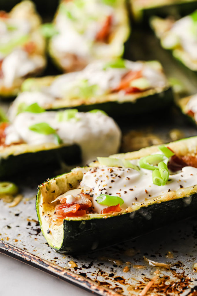 close-up image of loaded zucchini skins resting on a baking sheet atop a marble kitchen counter