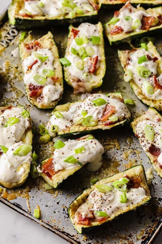 side angle shot of cooked zucchini skins topped with sour cream and chopped green onions atop a baking sheet