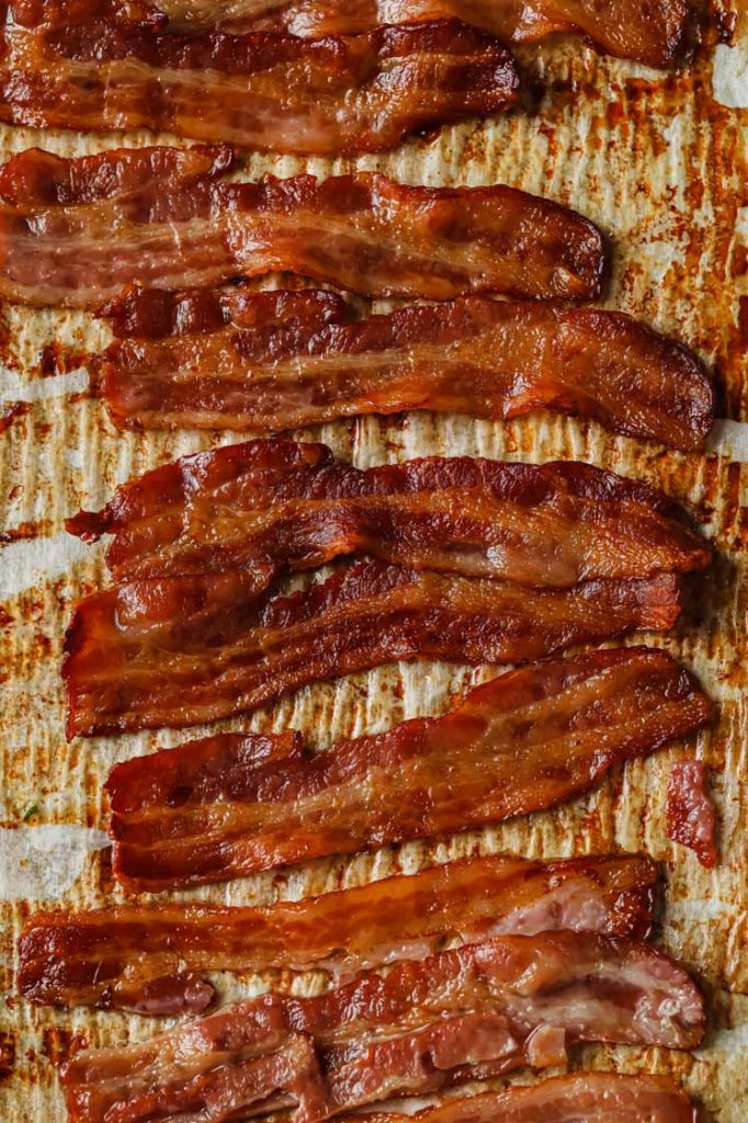 oven cooked bacon layered on a baking sheet.