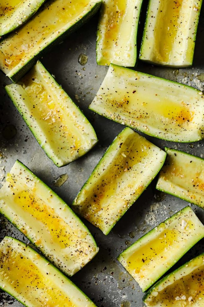 half sliced zucchinis with the insides scooped out in a large baking sheet and toss with avocado oil before sprinkling each slice with garlic, onion powder, salt, and pepper.