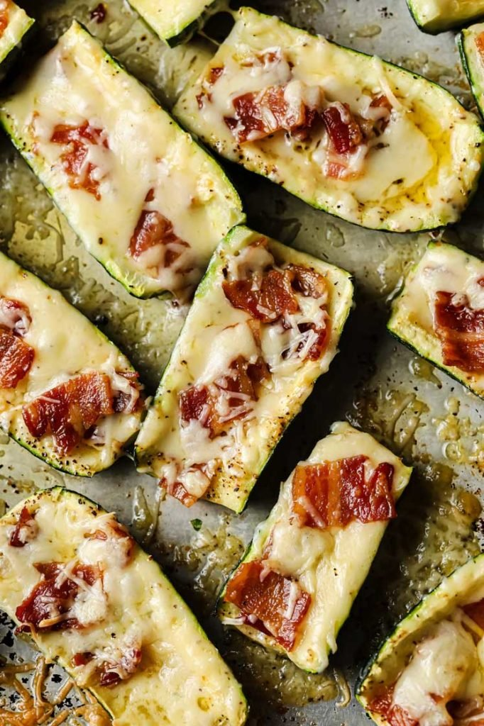 baked zucchini skins with bacon bits and melted cheese on a large baking sheet.