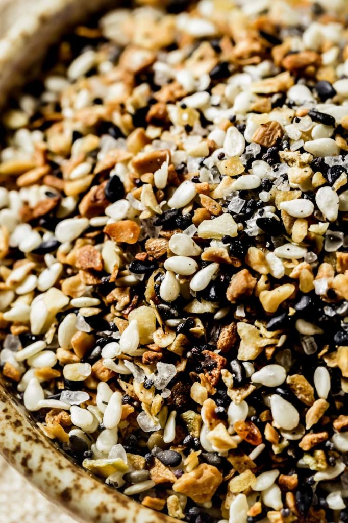 angled image of a bowl of everything bagel seasoning atop marble kitchen counter.