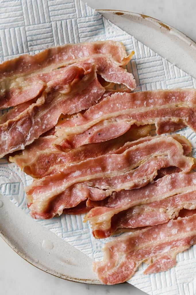 bacon strips fresh out of the oven resting on a parchment paper lined plate atop a marble kitchen table.