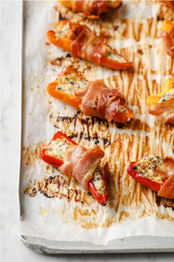 bacon-wrapped pepper popper out of the oven resting on a baking sheet.