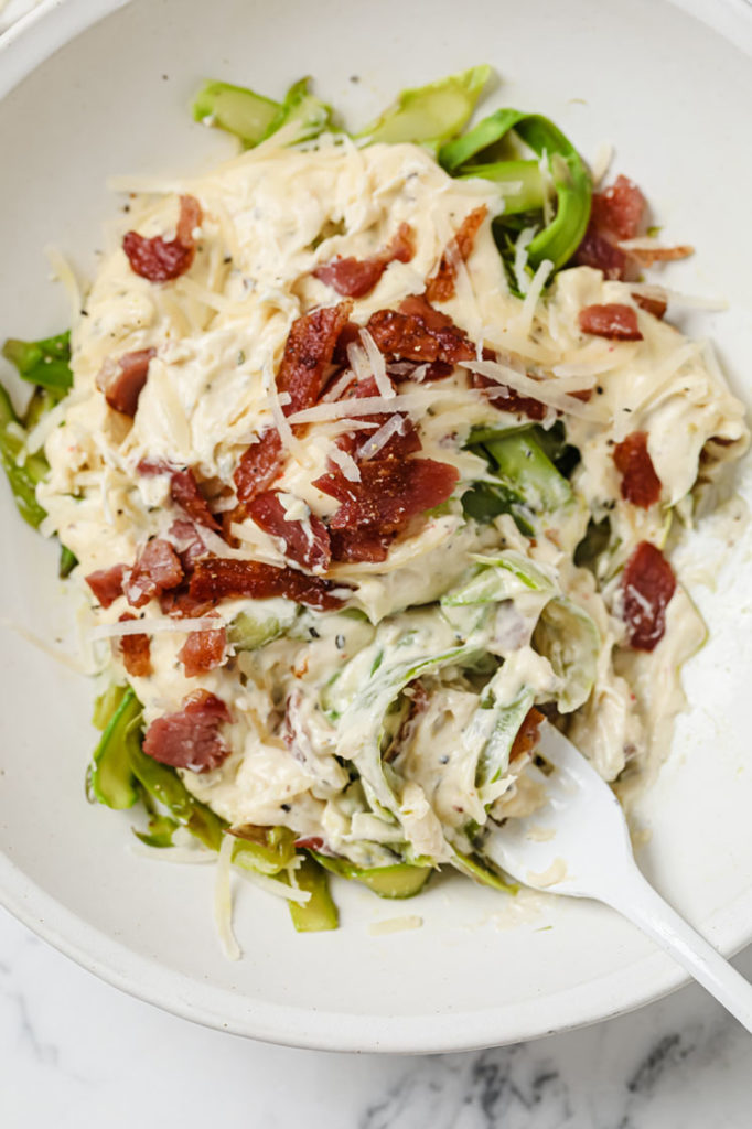 overhead shot of asparagus pasta with fork white in white bowll