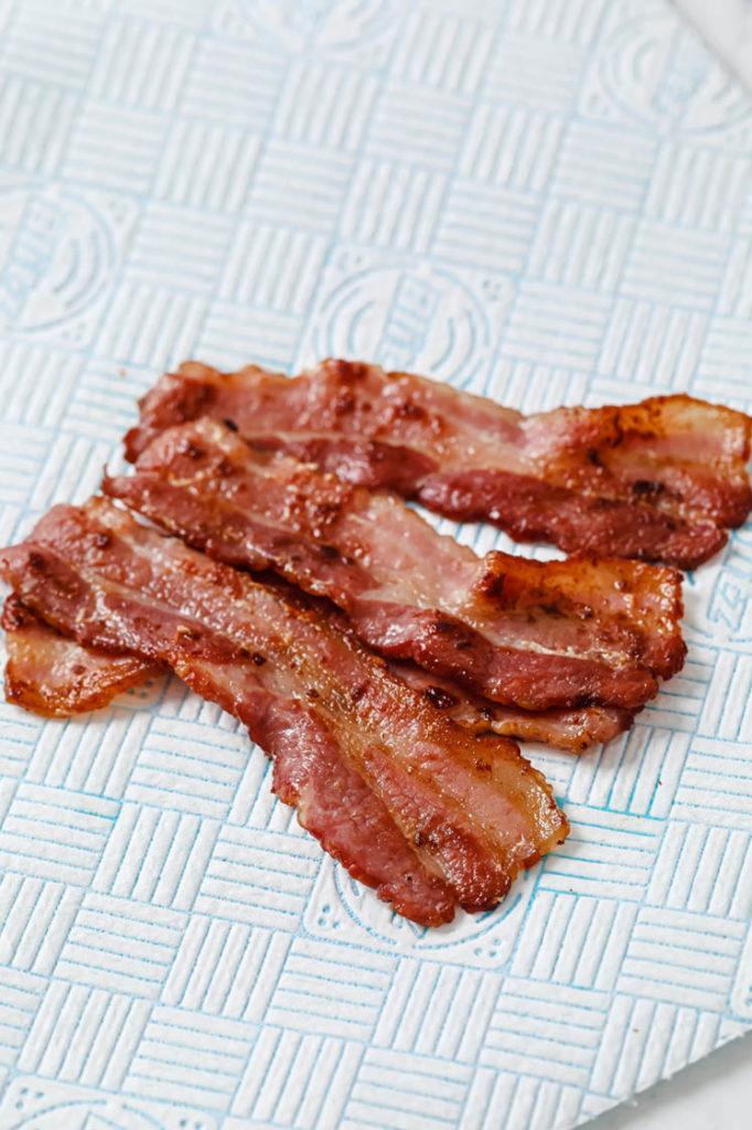 cooked bacon de-greasing atop paper towel