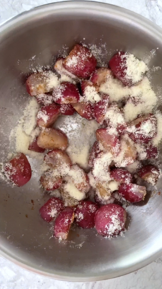 spices and grated parmesan cheese on top of radishes in stainless steel bowl