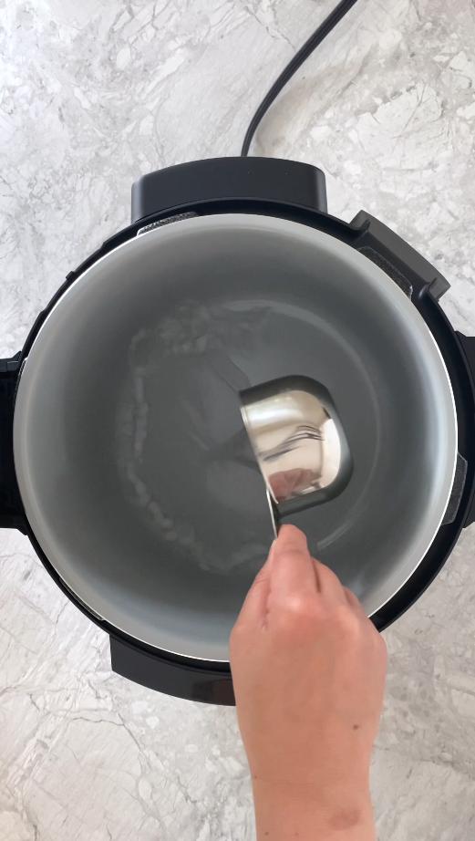 measuring cup pouring water into ninja foodi